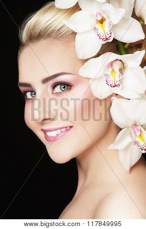 Close-up portrait of young beautiful healthy happy woman with fresh make-up and white orchid