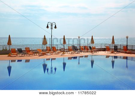 Few Orange Loungers And Parasol Standing Near To Open Pool, Sea