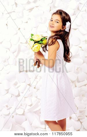 Beautiful little girl in white dress with a bouquet of flowers in her hands posing by a background of white paper flowers. Kids fashion. Cosmetics, accessories.