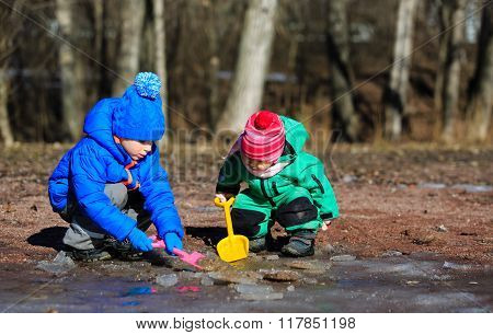 little boy and girl playing with water in spring