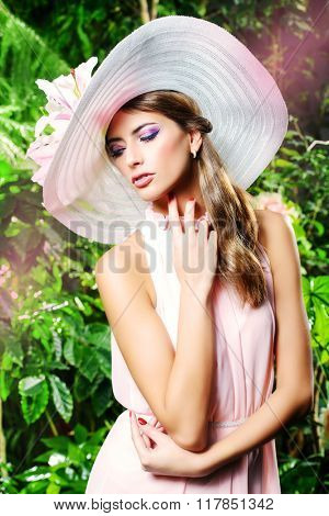 Beautiful romantic woman in light dress and elegant hat posing in a blooming garden. Beauty, fashion.