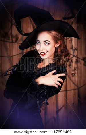 Portrait of a beautiful witch lady in black dress and black hat. Halloween concept.