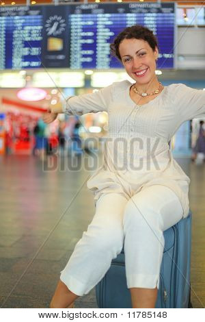 Beautiful Young Woman Sitting On Their Luggage In Hall Of Airport And Stretching Arms