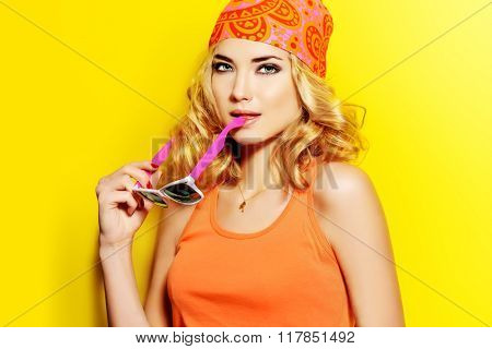 Pretty girl with curly blonde hair wearing bright clothes and sunglasses posing over yellow background. Bright style, fashion.
