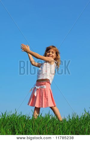 Joyful girl stands in field with green grass against blue sky