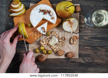 Hands Cut Pear On Wood Table With Food. Top View