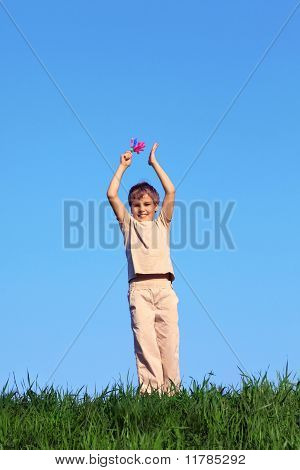 Smiling boy standing and holds up his hands raised in rattle