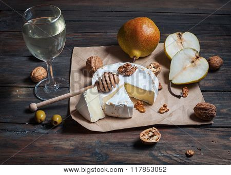 Camembert Cheese With Walnuts, Honey And Pears On Rustic Table. Glass Of White Wine