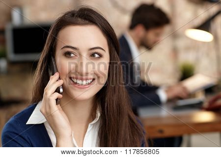 Closeup portrait of attractive young businesswoman talking on mobilephone, looking away, smiling.