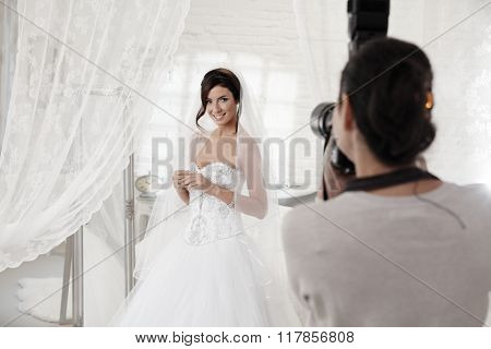 Beautiful bride posing front of photographer in white interior.