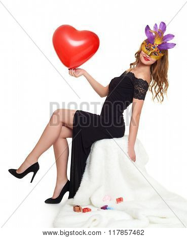 Young woman in black evening gown and carnival mask. Sit on white fur. Heart shaped balloon in hand. Holiday and party concept.
