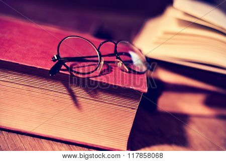 closeup of a pair of retro round-framed eyeglasses and some old book on a rustic wooden table, with a filter effect