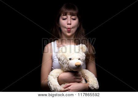 Grimacing teenage girl with teddy bear