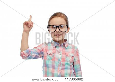 childhood, school, education, vision and people concept - happy little girl in eyeglasses pointing finger up