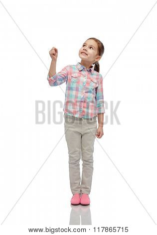 childhood, fashion, imagination and people concept - happy little girl looking up and holding in hand something invisible