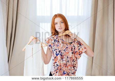 Thoughtful attractive young woman choosing clothes and deciding what to put on