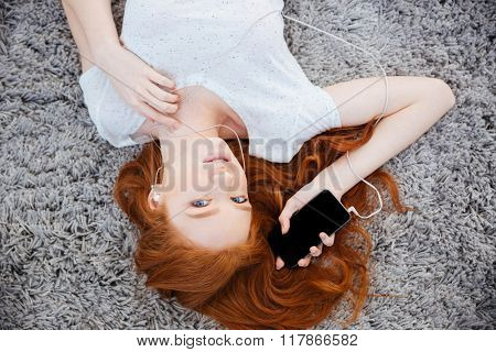 Lovely redhead woman lying on the carpet and listening music on smartphone