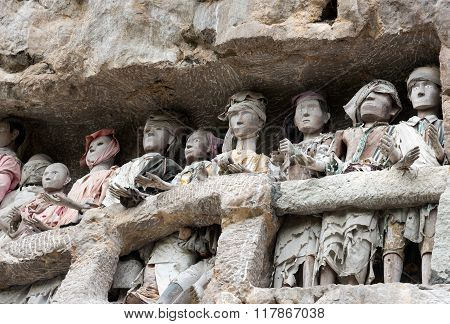 Tana Toraja, Indonesia - Dec 08, 2015: Wooden statues of Tau Tau are representatives of the deceased and guard the tombs. Suaya is cliffs old burial site of the royal family of Sangalla in Tana Toraja. South Sulawesi Indonesia
