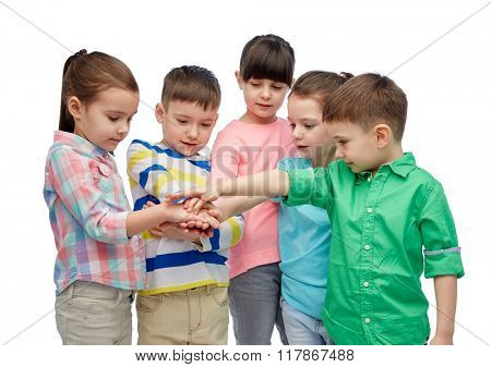 childhood, fashion, friendship and people concept - happy little children with hands on top