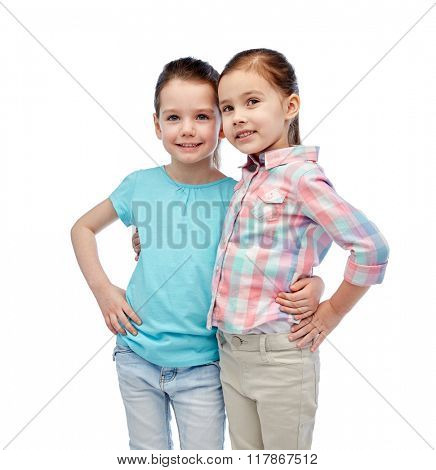 childhood, fashion, friendship and people concept - happy smiling little girls hugging