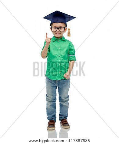 childhood, school, education, knowledge and people concept - happy boy in bachelor hat or mortarboard and eyeglasses pointing finger up