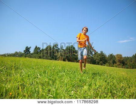 Boy enjoying summertime running through a sunny meadow in a summer forest