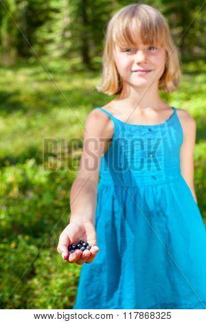 Girls wearing blue summer dress showing fresh blueberries, focus on her palm