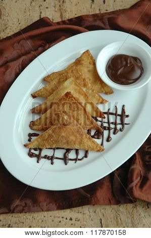 Dessert fried wontons with chocolate sauce on plate