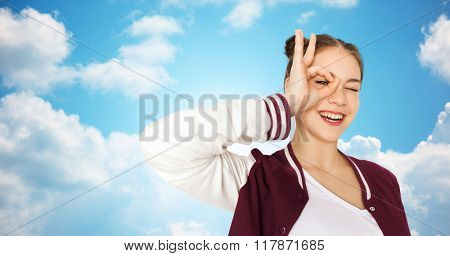people and teens concept - happy smiling pretty teenage girl making face and having fun over blue sky and clouds background