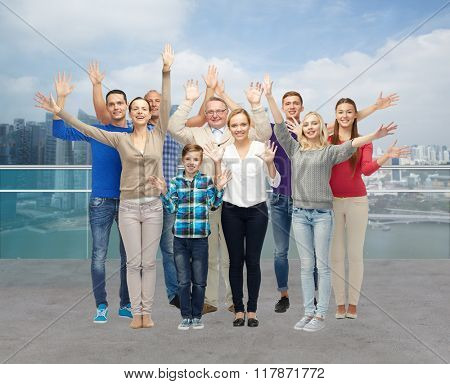 tourism, travel, generation and people concept - group of smiling men, women and boy waving hands over singapore city waterside background