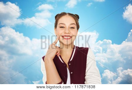 people and teens concept - happy smiling pretty teenage girl with eye makeup over blue sky and clouds background