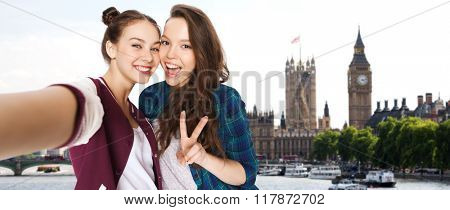 people, travel, tourism and friendship concept - happy smiling pretty teenage girls taking selfie and showing peace sign over london background