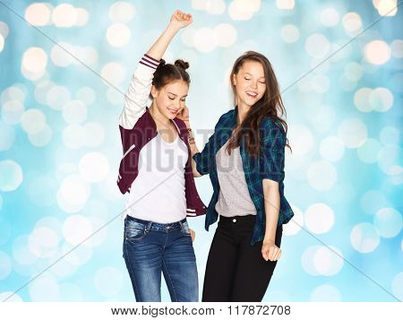 people, fun, teens and friendship concept - happy smiling pretty teenage girls dancing over blue holidays lights background
