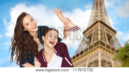 people, travel, tourism and friendship concept concept - happy smiling pretty teenage girls showing peace hand sign over eiffel tower in paris background