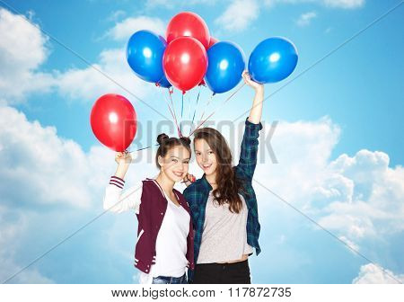 people, friends, teens, holidays and party concept - happy smiling pretty teenage girls with helium balloons over blue sky and clouds background