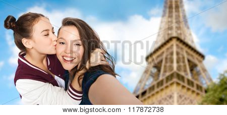 people, travel, tourism and friendship concept - happy smiling pretty teenage girls taking selfie and kissing over eiffel tower in paris background