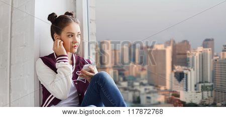people, technology and teens concept - sad pretty teenage girl sitting on windowsill with smartphone and earphones listening to music over city background