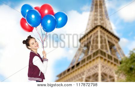 people, travel, tourism and holidays concept - happy smiling pretty teenage girl with helium balloons over eiffel tower in paris background