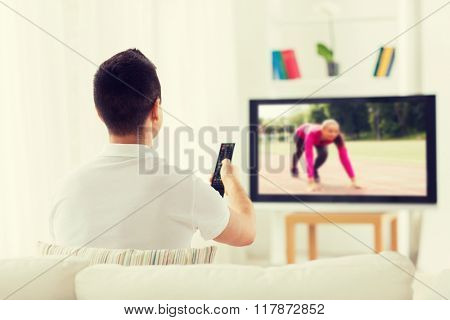 leisure, technology, mass media and people concept - man with remote control watching sport channel on tv at home from back