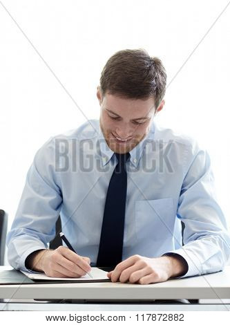 business, people and work concept - smiling businessman sitting and writing or signing papers in office
