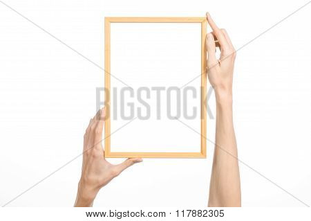 House Decoration And Photo Frame Topic: Human Hand Holding A Wooden Picture Frame Isolated On A Whit