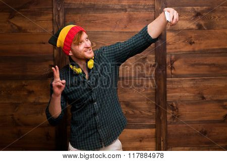 Hipster man making selfies over wooden