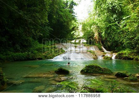 Unidentified female tourist swimming in the Reach Falls, Portland, Jamaica..