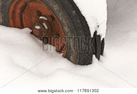 Old Tractor Wheel In Snow.