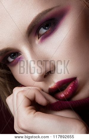 Beautiful blonde woman in a red sweater with bright makeup and dark lips. Beauty face. Close-up port