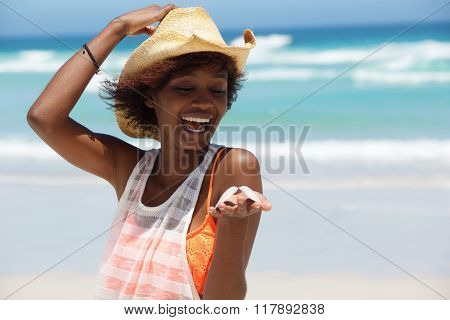African American Woman With Shell In Hand At The Beach
