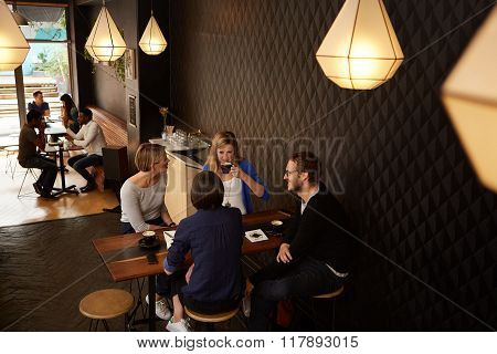 Friends talking while enjoying fresh coffee in a cafe together