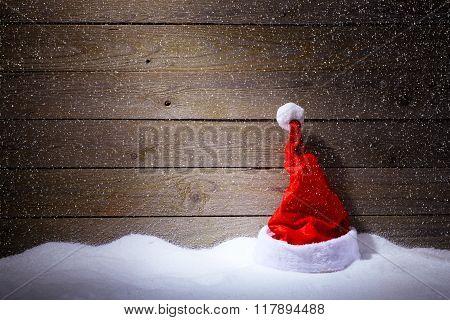 Santa Hat In Snow On Wooden Background