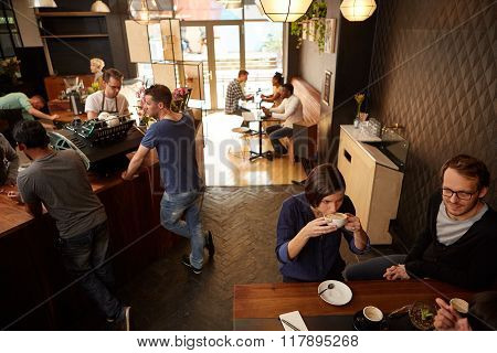 Modern coffee shop with contented customers sitting and standing