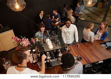 Multi-racial couple laughing with the baristas at a cafe